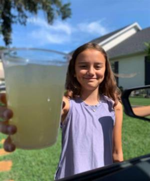 NCES Student Myah Gibson holding a glass of lemonade