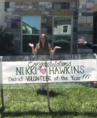 Photo of Nikki Hawkins with a Congratulations Nikki Hawkins District Volunteer of the Year banner
