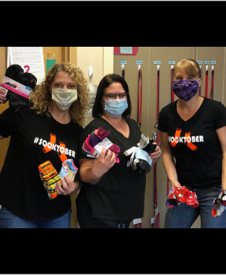3rd Grade Teachers: Mrs. Massey, Mrs. Malcolm and Mrs. Barton wearing #socktober shirts and holding pairs of socks.
